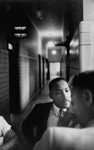 Martin Luther King in hallway as he learns his fine has been paid, Montgomery, Alabama Police Headquarters, 1958 Archival Pigment Print