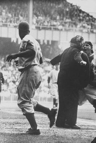 Brooklyn Dodger Jackie Robinson after stealing home base in the 8th inning of the 1st game of the World Series at Yankee Stadium<br/>