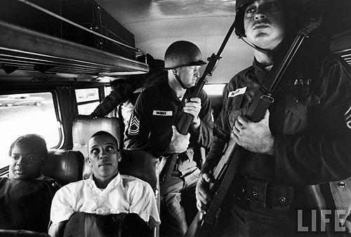 Freedom Riders Julia Aaron & David Dennis sitting on board interstate bus as they and 25 others are escorted by 2 National Guardsmen holding bayonets, on way from Montgomery, AL to Jackson, MS, May, 1961 - Photo by Paul Schutzer Gelatin Silver print