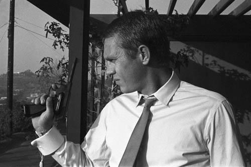 Steve McQueen with pistol at his Hollywood Hills home, 1961 Gelatin Silver print