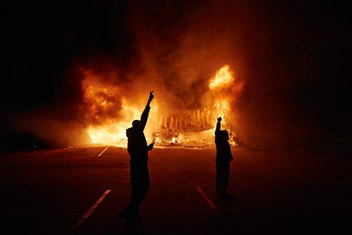 Onlookers stand on West Florissant Avenue as an AutoZone burns early Tuesday, Nov. 25, 2014 in Dellwood, Mo. A grand jury decided not to charge Ferguson police officer Darren Wilson in the fatal shooting of Michael Brown. Archival Pigment Print