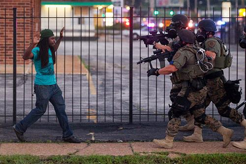 Rashaad Davis, 23, backs away as St. Louis County police officers approach him with guns drawn and eventually arrest him, Ferguson, Missouri, August 11, 2014<br/>