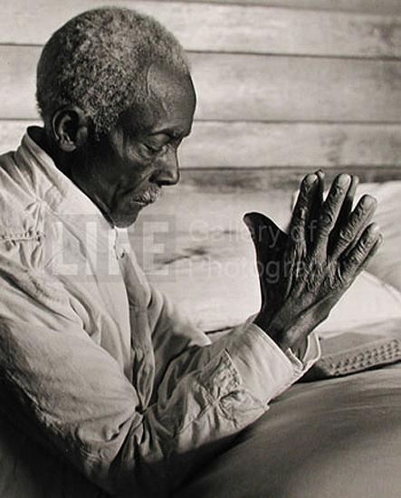 African American sharecropper saying his evening prayers as he kneels at bedside at home., 1936 Gelatin Silver print