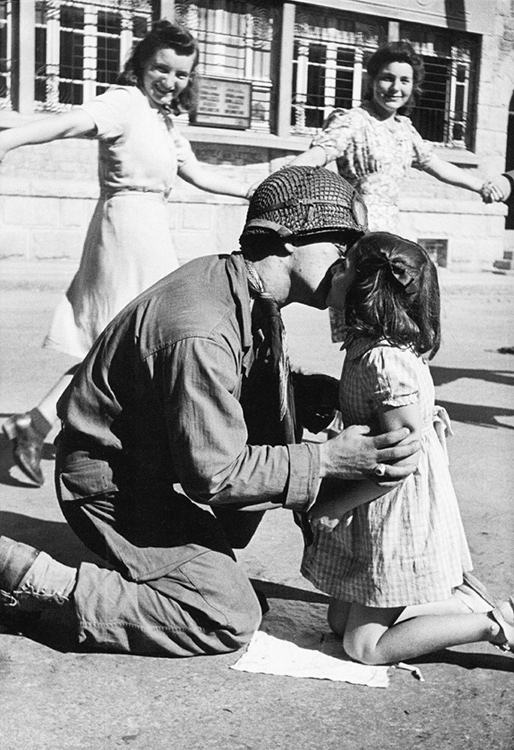 Kiss of Liberation: Sergeant Gene Costanzo kneels to kiss a little girl during spontaneous celebrations in the main square of the town of St. Briac, France, August 14, 1944