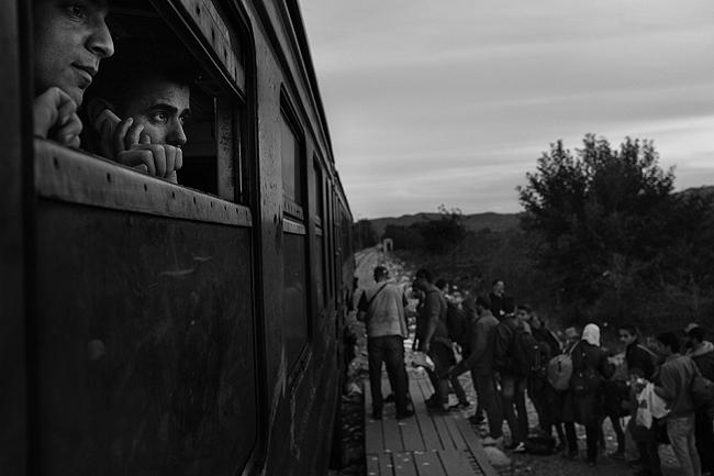 Rwand Ali, from Syria, watches refugees board a train to the Serbian border, 2015<br/>