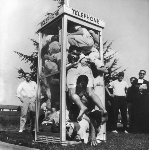 Joe Munroe; Twenty-two exuberant St. Mary's College students folded and stacked inside an on campus phone booth in an attempt to set a record for phone booth cramming, Moraga, California, March 26, 1959 Gelatin Silver print