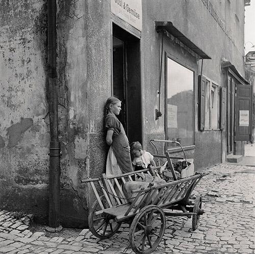 Waiting For Mom. Two children wait outside a grocery store with the family shopping cart, Hoescht, Germany, 1946. <br/>