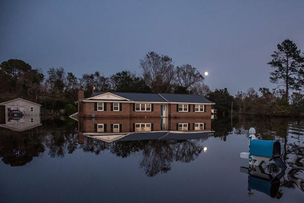 A home illuminated by moonlight sits still in the water of a flooded community at Rocky Point, 2018 Archival Pigment Print