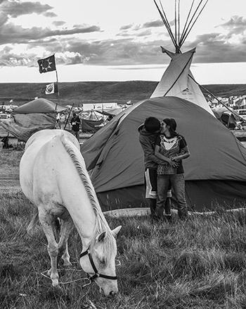 Hiding from view of nearby families, a young couple sneaks in a quick kiss while allowing a horse to graze on Oceti Sakowin grass, September 8, 2016 Archival Pigment Print