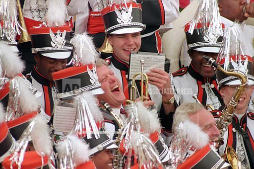 President-elect Bill Clinton leans back and laughs as he plays the saxophone with the Sugar Bear marching band of Central High School during a City Hall rally in Macon, Ga, November 23, 1992 Chromogenic print