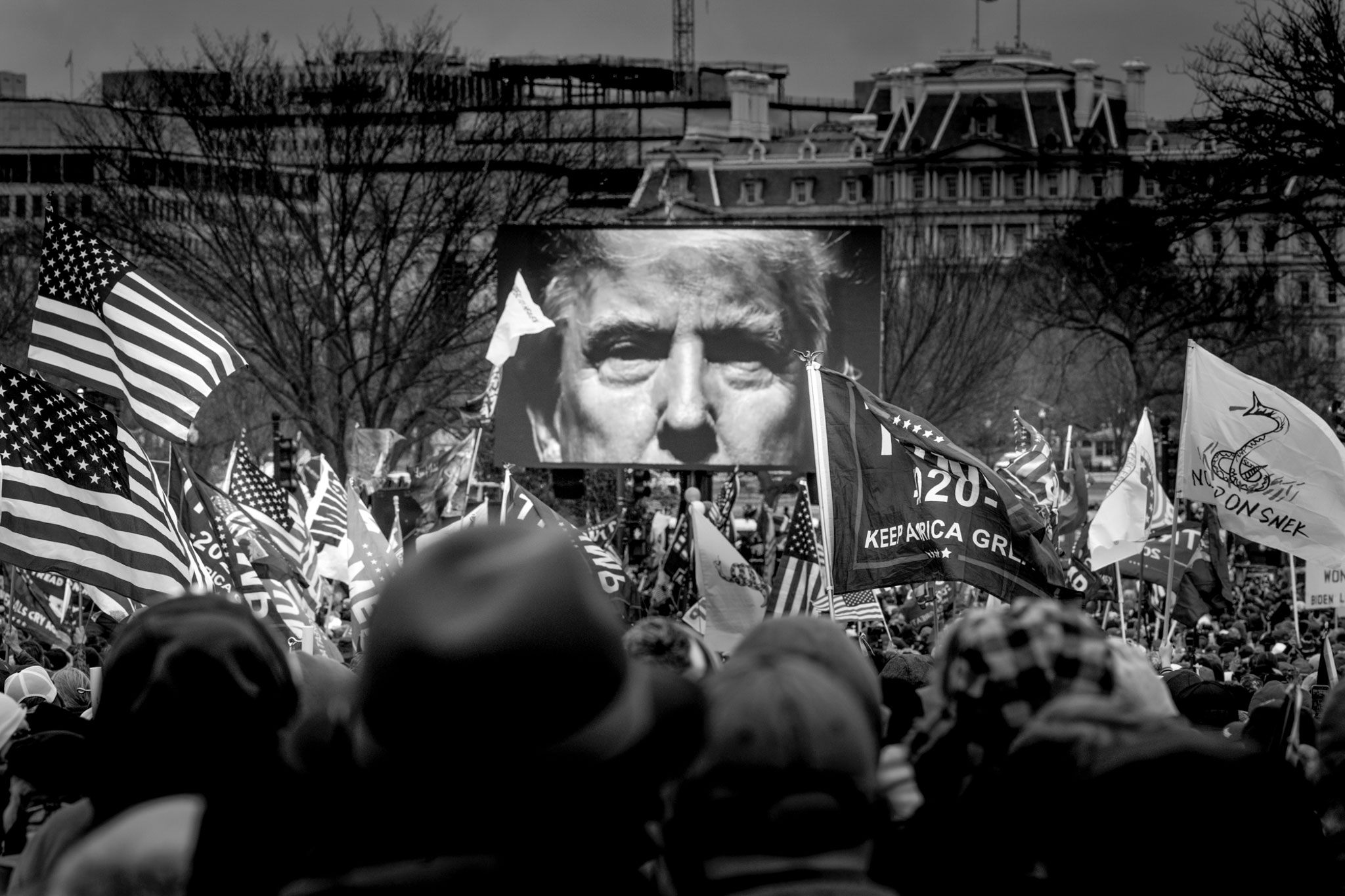 President Trump's image appears onscreen at a rally outside the White House. Before long, a mob of his supporters would march into the Capitol building, January 6, 2021