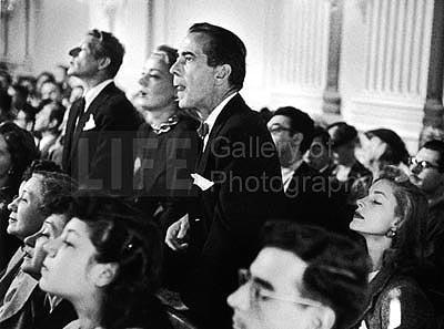 Actors Danny Kaye, June Havoc and Humphrey Bogart, with wife, actress Lauren Bacall sitting beside him, listening intently a hearing regarding communists in the film industry, 1947<br/>