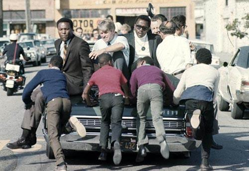 The Kennedy campaign travels through the Watts section of Los Angeles on the last day before the primary, 1968 Archival Pigment Print
