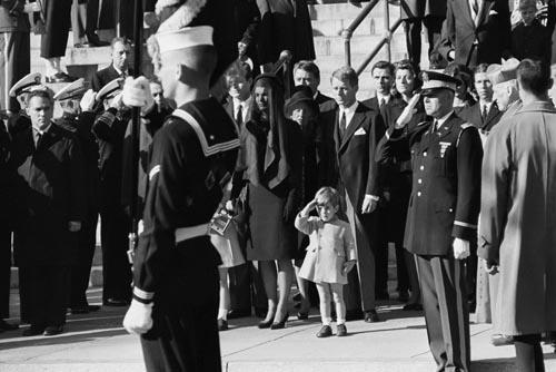 John F. Kennedy Jr. saluting his father's coffin, November 25, 1963 with Ted Kennedy, Jacqueline Kennedy, Rose Kennedy, Peter Lawford, and Robert F. Kennedy in background.<br/>