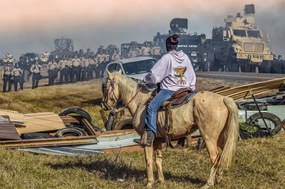 Native American woman on horse facing police line at Standing Rock