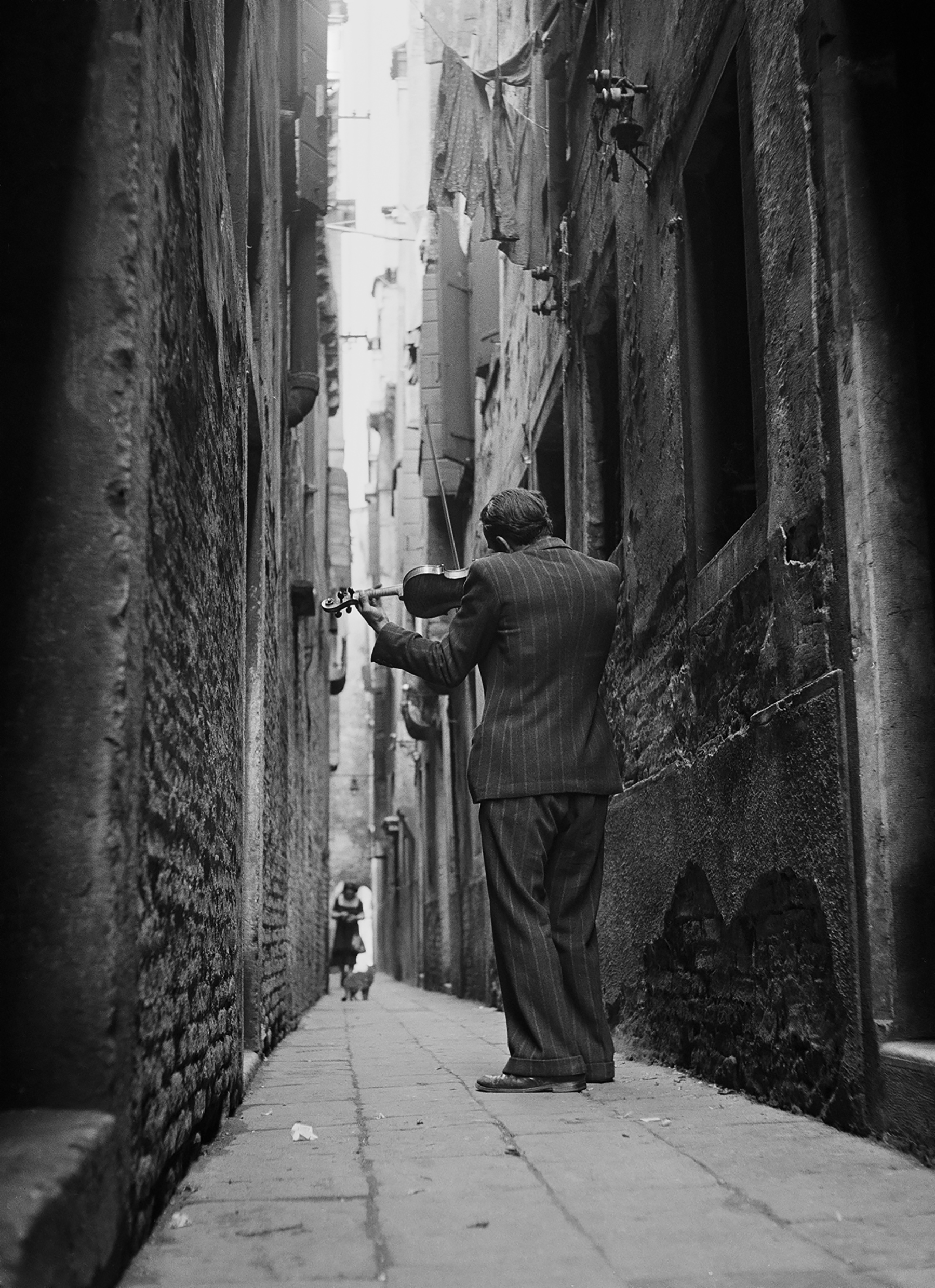 Tony Vaccaro black and white photograph of a violinist on street in in Venice, Italy, 1947